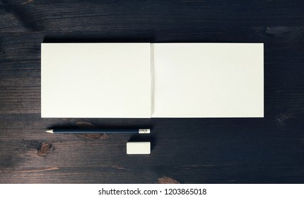 Photo of open sketchbook with blank pages, pencil and eraser on wooden background. Responsive design template. Flat lay.