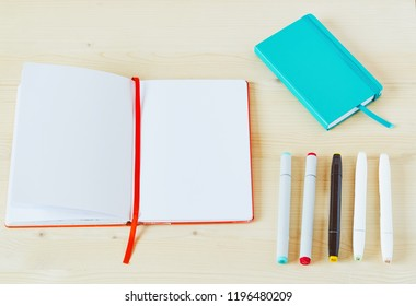 Photo of open sketchbook with white copy space on light wooden table. With five markers and a teal sketchbook