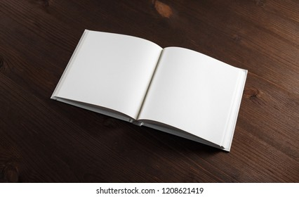 Photo of opened book with blank white pages on wooden background.
