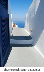 Photo of opened door and beautiful white street in Santorini island, Greece