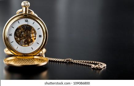 Photo of opened old vintage pocket clock against the black background