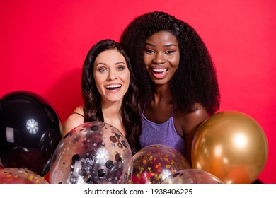 Photo of optimistic brunette ladies hold balloons wear tops isolated on vibrant red color background