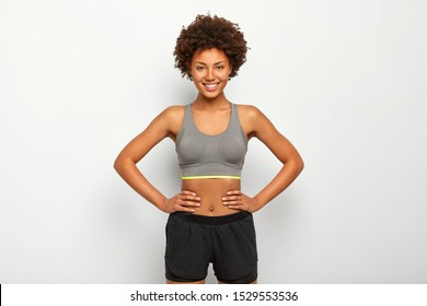 Photo of optimistic dark skinned sporty woman keeps hands on waist, smiles happily, dressed in sport bra and black shorts, isolated over white background, has fit?ess training with instructor