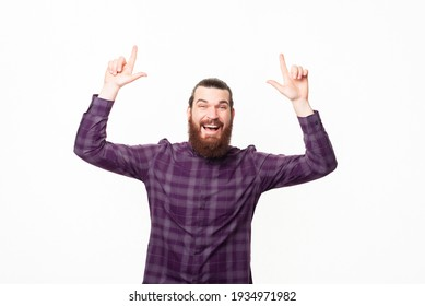 Photo of optimistic happy young bearded man pointing up.