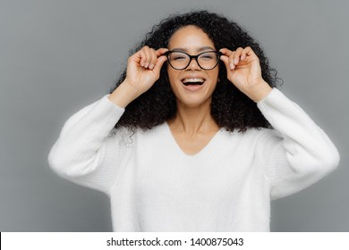 Photo of optimistic lovely woman looks happily through spectacles, keeps hands on rim of spectacles, notices something pleasant, wears white sweater, isolated over grey background. Happiness