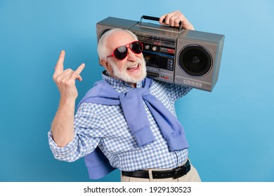 Photo of optimistic old grey hairdo man show rock sign hold boom-box wear spectacles blue shirt isolated on color background