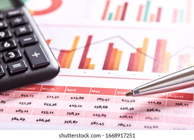 Photo of orange financial and planning chart with black calculator and silver pen. Space for your text.