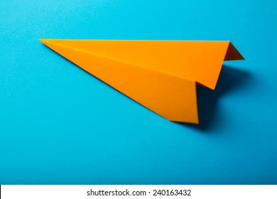 Photo of orange origami paper airplane on blue paper background