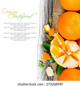 Photo of oranges with slices and leaves on wooden board with white space