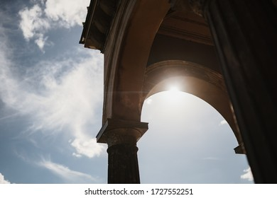 photo of an outside arc hallway with the sky in the background