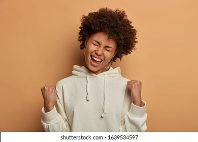Photo of overemotive curly ethnic woman rejoices praises or winning competition, makes fist pump with closed eyes, tilts head and smiles happily, stands in triumph pose, wears casual white hoodie