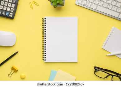 Photo overhead of notebook keyboard calculator pen computer mouse notes plant glasses and paperclips isolated bright color yellow backdrop