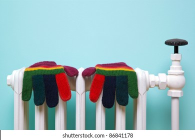 Photo of a pair of hand knitted striped woolen gloves drying on an old traditional cast iron radiator.
