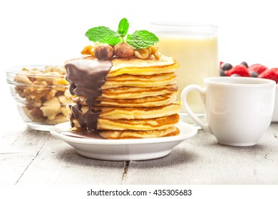 Photo of pancakes with chocolate and nuts over wooden table