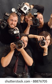 Photo of paparazzi fighting for space to take photos. Focus on the female in front.