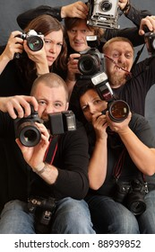 Photo of paparazzi fighting for space to take photos. Focus is on the face of the male in front.