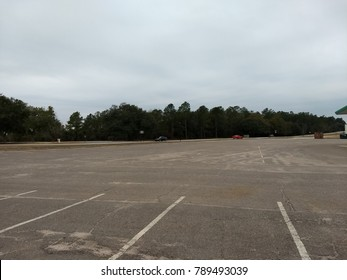 A photo of a parking lot and trees in the distance.