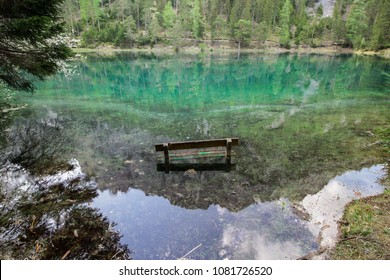 Photo of a partially sinked bench, as found at the Green Lake, in Styria, Austria. Crystal clear mountain lake, emerald green water, landscape reflecting in it.