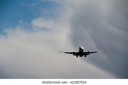 Photo of a passenger airplane in dark shadow on cloudy sky.