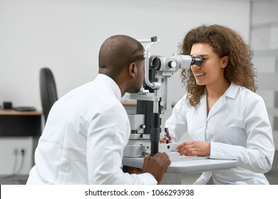 Photo of patient looking at medical apparatus during vision checking in ophthalmological laboratory with expirienced ophthalmologist..Trying to improve vision in modern oculist' cabinet.