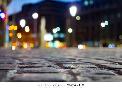 photo of pavement and blurred city light during night time