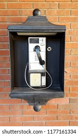 A photo of a payphone in a black box against a brick wall.