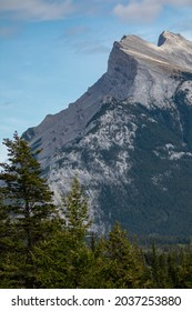 Photo of the peak of Mount Rundle in Alberta. This was taken on a summer day. The sky is mostly clear with a  few small clouds.