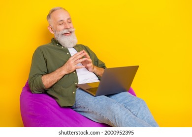 Photo of pensioner man sit beanbag hold computer look screen wear green shirt isolated yellow color background
