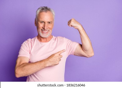 Photo of pensioner old man raise arm direct finger demonstrate biceps wear pink t-shirt isolated purple color background