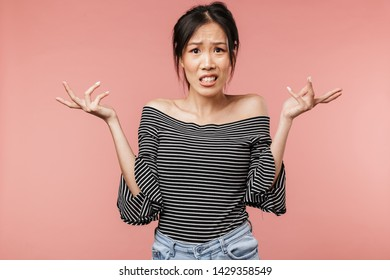 Photo of perplexed asian woman dressed in basic wear throwing up arms and looking at camera isolated over red background in studio