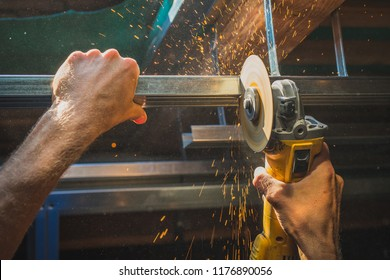 Photo of person cutting holders, aluminium profiles or aluminium structural frames that hold drywall boards with an angle grinder in house that is being rebuilt.Work on the roof using an angle grinder
