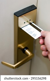 Photo of person's hand inserting a key card into a hotel room electronic door security lock to unlock the door.