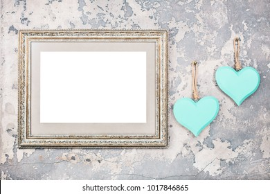 Photo or picture frame blank and two handmade Valentine's day love hearts hanging on vintage aged grunge textured concrete wall background. Retro old style filtered photo