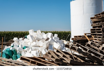 A photo of a pile of discarded white plastic containers and wood pallets on a farm.