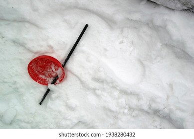 Photo of a plastic drink lid with a straw in the snow.