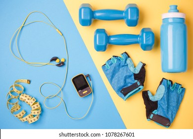 Photo of player, dumbbells, bottle of water, centimeter tape, gloves on blue and yellow background