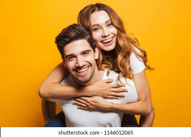 Photo of pleased adorable couple having fun while man piggybacking beautiful woman isolated over yellow background