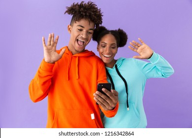 Photo of pleased african american brother and sister wearing colorful sweatshirts using mobile phone isolated over violet background