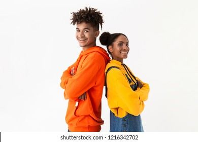Photo of pleased african american couple in colorful clothes smiling while standing back to back isolated over white background