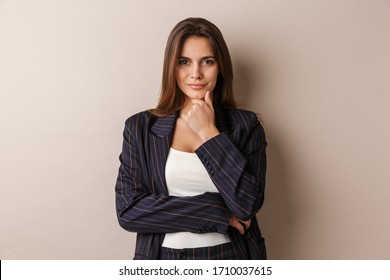 Photo of pleased businesswoman in formal suit posing and looking at camera isolated over white background