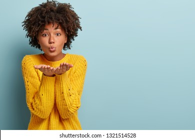 Photo of pleased dark skinned woman has Afro haircut, stretches hands near face, blows air kiss, expresses love and affection, isolated over blue background, free space aside for your promotion