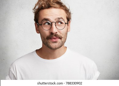 Photo of pleased dreamy male wonk with trendy hairdo, wears spectacles and casual white t shirt, imagines something pleasant, looks upwards with intriguing expression, isolated on concrete wall