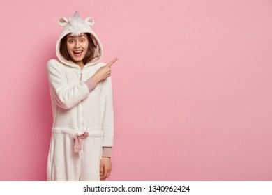 Photo of pleased lovely young woman with satisfied expression, dressed in sleepwear, points aside on upper right corner, has positive look, isolated over pink background. Advertisement concept
