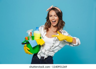 Photo of pleased young housemaid 20s wearing yellow rubber gloves for hands protection holding bucket with cleaning supplies isolated over blue background
