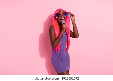 Photo portrait of african american woman singing wearing funny star glasses isolated on pastel pink colored background