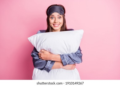 Photo portrait of amazed girl hugging pillow isolated on pastel pink colored background