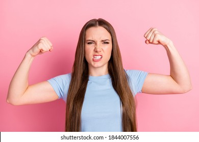 Photo portrait of angry woman flexing showing biceps isolated on pastel pink colored background