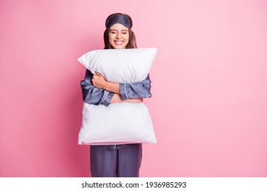Photo portrait of cheerful woman hugging pillow with two hands isolated on pastel pink colored background