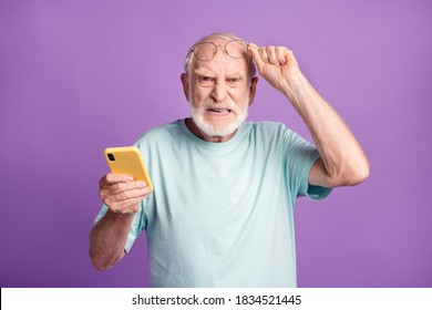 Photo portrait of cranky old man lifting up glasses holding phone in one hand isolated on vivid violet colored background
