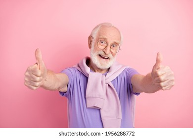 Photo portrait of elder man cheerful overjoyed showing thumb-up like sign isolated on pastel pink color background